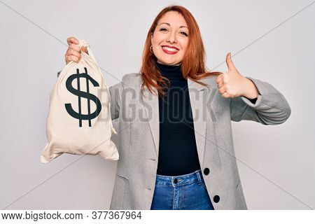 Young beautiful redhead woman holding bag with money and dollar sign over white background happy with big smile doing ok sign, thumb up with fingers, excellent sign