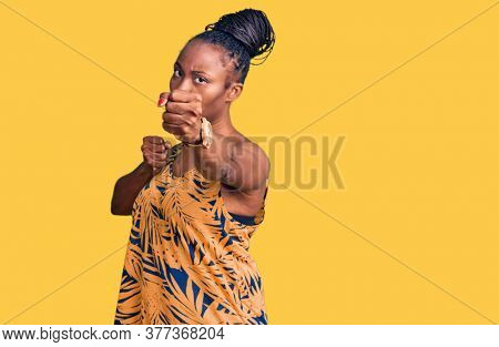 Young african american woman wearing casual clothes punching fist to fight, aggressive and angry attack, threat and violence