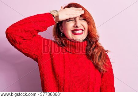 Young beautiful redhead woman wearing red casual turtleneck sweater over pink background surprised with hand on head for mistake, remember error. Forgot, bad memory concept.