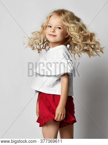 Beautiful Positive Little Blonde Girl With Curly Hair In Stylish Casual White Shirt And Red Shorts M