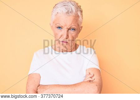 Senior beautiful woman with blue eyes and grey hair wearing classic white tshirt over yellow background skeptic and nervous, disapproving expression on face with crossed arms. negative person.