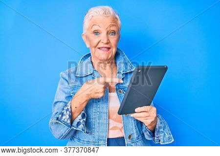 Senior beautiful woman with blue eyes and grey hair using touchpad device smiling happy pointing with hand and finger