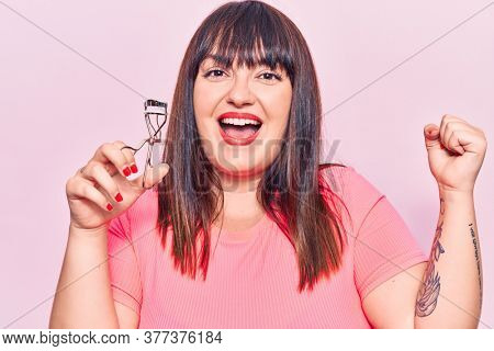 Young plus size woman holding eyelash curler screaming proud, celebrating victory and success very excited with raised arms