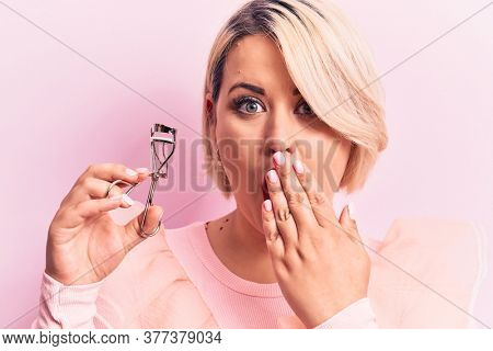 Young beautiful blonde plus size woman holding eyelash curler over isolated pink background covering mouth with hand, shocked and afraid for mistake. Surprised expression