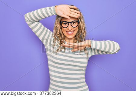 Beautiful blonde woman wearing casual striped t-shirt and glasses over purple background Smiling cheerful playing peek a boo with hands showing face. Surprised and exited