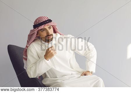 Pensive Arab Businessman Sitting In A Chair Thinks Looks Up On A Gray Background. Portrait Of An Att