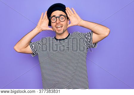 Handsome man with blue eyes wearing striped t-shirt and french beret over purple background Smiling cheerful playing peek a boo with hands showing face. Surprised and exited