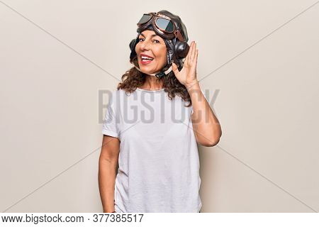 Middle age brunette woman wearing goggles and retro aviator leather hat over white background smiling with hand over ear listening and hearing to rumor or gossip. Deafness concept.