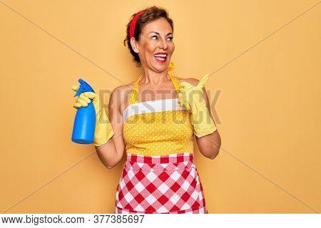 Middle age senior housewife pin up woman wearing 50s style retro dress cleaning using spray pointing and showing with thumb up to the side with happy face smiling