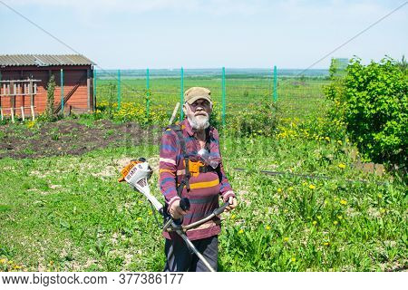 Elderly Man Mows Grass In His House With An Electric Trimmer.