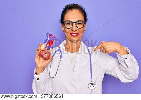 Middle age senior cardiologist doctor woman holding professional cardiology heart with surprise face pointing finger to himself