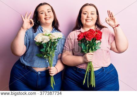 Young plus size twins holding flowers doing ok sign with fingers, smiling friendly gesturing excellent symbol