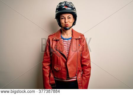 Middle age motorcyclist woman wearing motorcycle helmet and jacket over white background puffing cheeks with funny face. Mouth inflated with air, crazy expression.