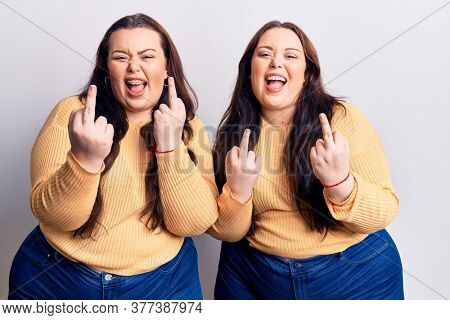 Young plus size twins wearing casual clothes showing middle finger doing fuck you bad expression, provocation and rude attitude. screaming excited