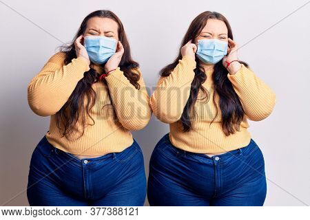Young plus size twins wearing medical mask covering ears with fingers with annoyed expression for the noise of loud music. deaf concept.