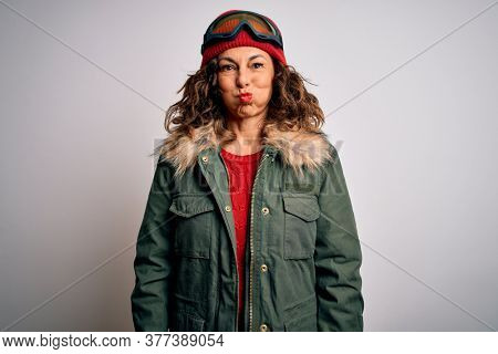 Middle age skier woman wearing snow sportswear and ski goggles over white background puffing cheeks with funny face. Mouth inflated with air, crazy expression.
