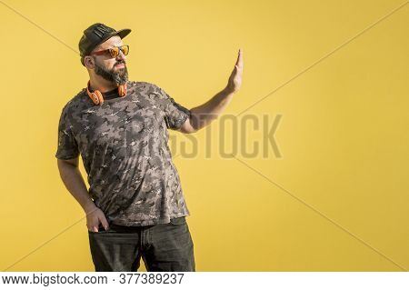 Curvy Man With Cap, Sunglasses With Disapproval Gesture With Yellow Background.