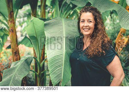 Curvy Woman Looking Straight Ahead Between Palm Leaves.