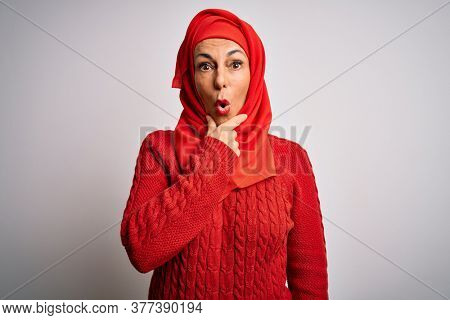 Middle age brunette woman wearing muslim traditional hijab over isolated white background Looking fascinated with disbelief, surprise and amazed expression with hands on chin