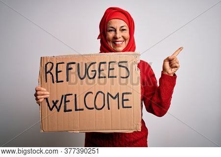 Woman wearing muslim hijab asking for immigration holding welcome refugees message very happy pointing with hand and finger to the side