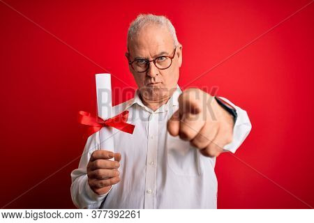 Middle age hoary student man wearing glasses holding university graduated degree diploma pointing with finger to the camera and to you, hand sign, positive and confident gesture from the front