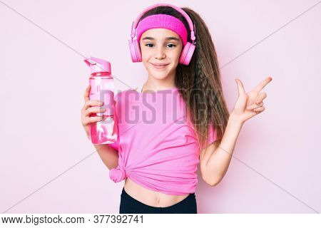 Cute hispanic child girl wearing gym clothes and using headphones holding bottle of water smiling happy pointing with hand and finger to the side