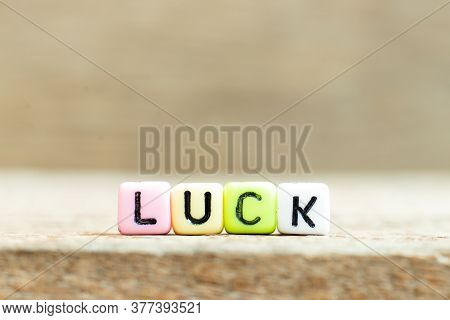 Colorful Bead With Black Letter In Word Luck On Wood Background