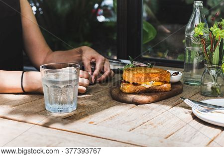Woman Having Egg Sandwiches With Cheese And Glass Of Fresh Water.