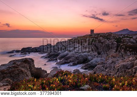Dawn Breaking Over The Silhouetted Genoese Tower At Punta Spano Near Lumio And The Rocky Coastline O