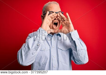 Middle age handsome hoary man wearing casual striped shirt and glasses over red background Shouting angry out loud with hands over mouth