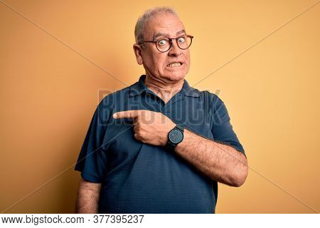 Middle age handsome hoary man wearing casual and glasses over yellow background Pointing aside worried and nervous with forefinger, concerned and surprised expression