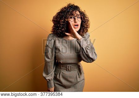 Beautiful arab business woman wearing dress and glasses standing over yellow background hand on mouth telling secret rumor, whispering malicious talk conversation