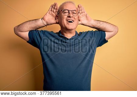 Middle age handsome hoary man wearing casual and glasses over yellow background Smiling cheerful playing peek a boo with hands showing face. Surprised and exited