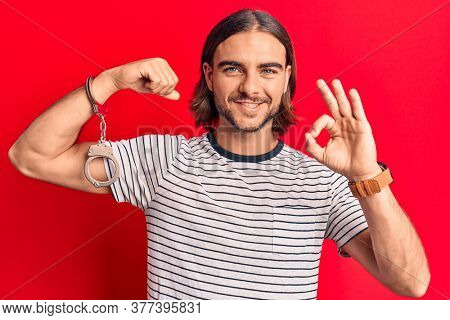 Young handsome man wearing prisoner handcuffs doing ok sign with fingers, smiling friendly gesturing excellent symbol