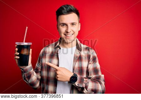 Young handsome caucasian man drinking a fresh soda refreshment over red background very happy pointing with hand and finger