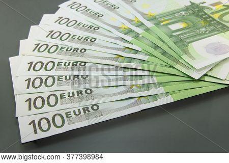 Stack Of Various One Hundred Euro Bills, One Hundred Euro Cash Bills On Dark Background.