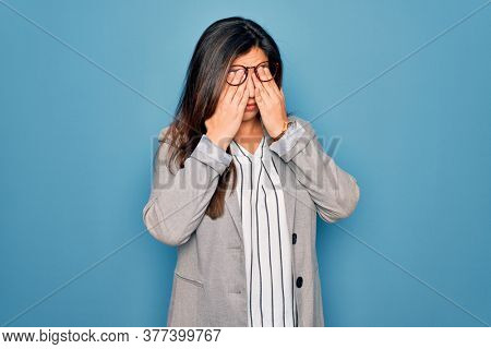 Young hispanic business woman wearing glasses standing over blue isolated background rubbing eyes for fatigue and headache, sleepy and tired expression. Vision problem