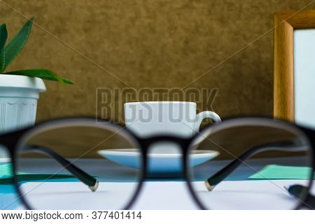 Black-rimmed Glasses In The Foreground. Behind Glasses A Cup Of Coffee