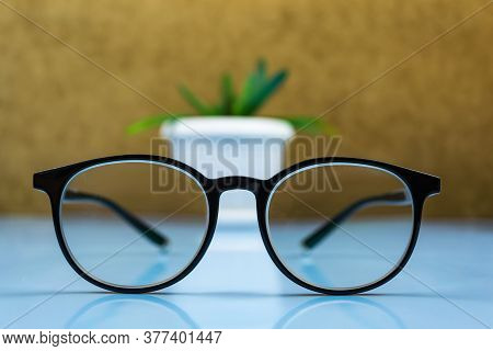Black-rimmed Glasses In The Foreground. Behind The Glasses Is A White Flowerpot With A Flower.