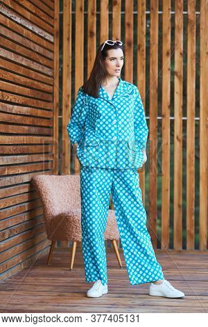 Woman Standing In Pajamas Pajamas With Polka Dots On Wooden Background In Full Length. Caucasian Fem