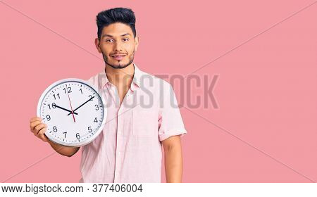Handsome latin american young man holding big clock looking positive and happy standing and smiling with a confident smile showing teeth