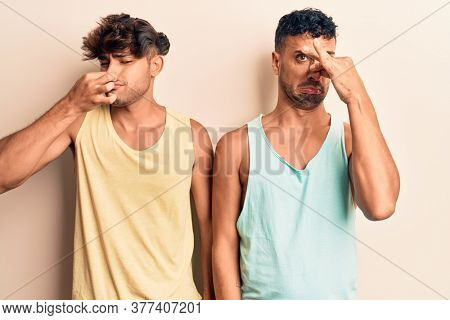 Young gay couple wearing casual clothes smelling something stinky and disgusting, intolerable smell, holding breath with fingers on nose. bad smell