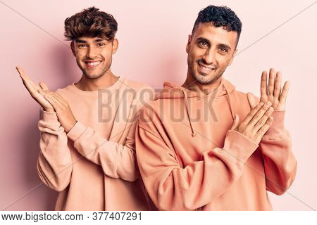 Young gay couple wearing casual clothes clapping and applauding happy and joyful, smiling proud hands together