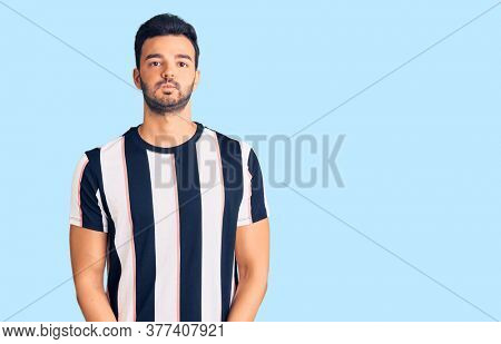 Young handsome hispanic man wearing striped tshirt puffing cheeks with funny face. mouth inflated with air, crazy expression.