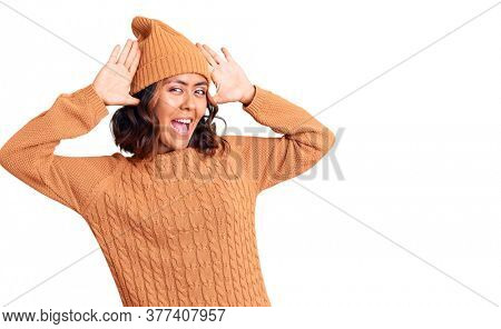 Young beautiful mixed race woman wearing wool sweater and winter hat smiling cheerful playing peek a boo with hands showing face. surprised and exited