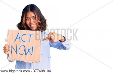 Young beautiful mixed race woman holding act now banner smiling happy pointing with hand and finger