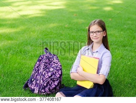 Back To School. Education Concept. Cute Smiling Schoolgirl In Glasses Sitting On Grass. Happy Little