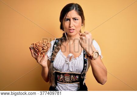 Young brunette german woman wearing traditional Octoberfest dress holding bowl with pretzels annoyed and frustrated shouting with anger, crazy and yelling with raised hand, anger concept