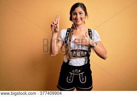 Young beautiful brunette german woman celebrating Octoberfest wearing traditional dress smiling swearing with hand on chest and fingers up, making a loyalty promise oath
