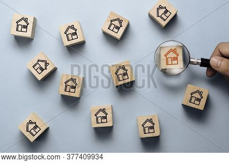 Hand Holding Magnifier Glass To Searching Red House Icon On Wooden Cube Block Among Black House Icon